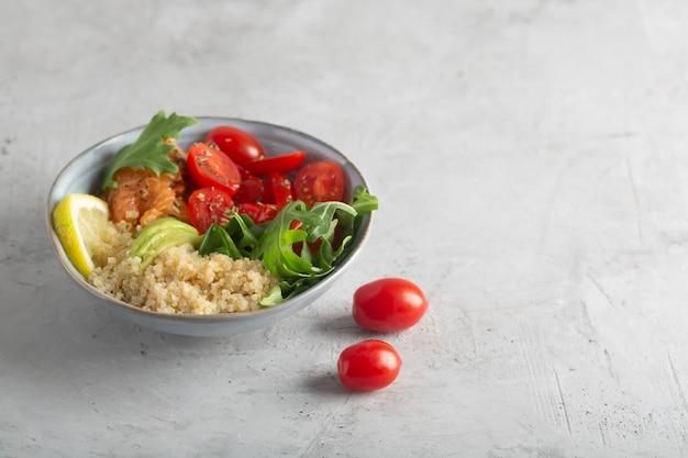 Sałatka dietetyczna z komosą ryżową, łososiem i warzywami, takimi jak pomidory i rukola. sałatka organiczna ze świeżych witamin.