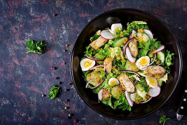 Sałatka dietetyczna z małżami, jajkami przepiórczymi, ogórkami, rzodkiewką i sałatą. zdrowe jedzenie. sałatka z owoców morza. widok z góry. leżał płasko.