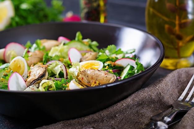 Sałatka dietetyczna z małżami, jajkami przepiórczymi, ogórkami, rzodkiewką i sałatą. zdrowe jedzenie. sałatka z owoców morza.