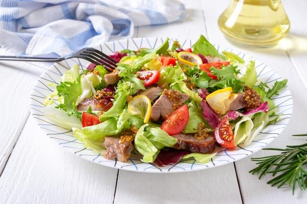Sałatka dietetyczna z piersią kaczki magre, świeżymi ziołami, warzywami i sosem musztardowym na jasnym drewnie