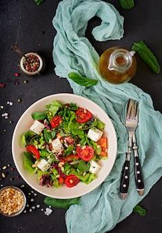 Sałatka dietetyczna z pomidorami, fetą, sałatą, szpinakiem i orzeszkami piniowymi. widok z góry. leżał płasko.