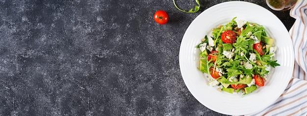 Sałatka dietetyczna z pomidorami, serem pleśniowym, awokado, rukolą i orzeszkami piniowymi. widok z góry. transparent