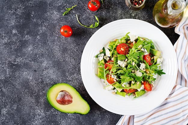 Sałatka dietetyczna z pomidorami, serem pleśniowym, awokado, rukolą i orzeszkami piniowymi.
