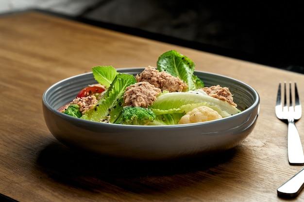 Sałatka dietetyczna z tuńczykiem, brokułami i pomidorkami cherry w misce na drewnianym tle. zbliżenie, selektywne ogniskowanie, ziarno szumu