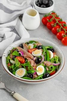 Sałatka francuska nicejska z tuńczykiem, jajkiem, fasolką szparagową, pomidorami, oliwkami, sałatą, cebulą i anchois na szarym betonowym tle.