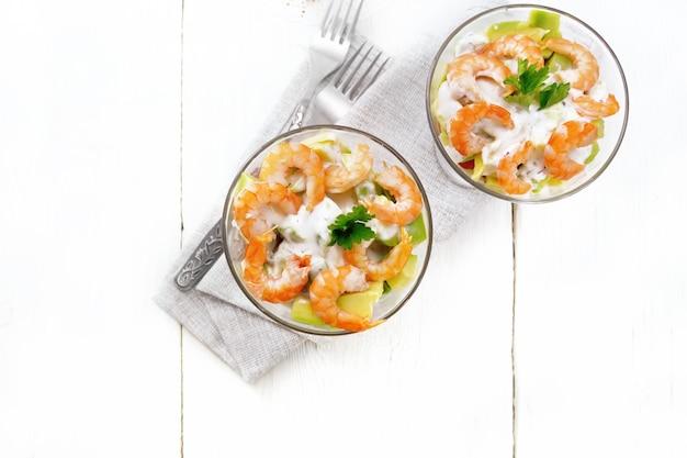 Sałatka francuska z krewetkami, awokado, świeżym ogórkiem, słodką papryką i pomidorem, doprawiona sosem jogurtowym w dwóch szklanych szklankach na serwetce, chlebie i widelcach na drewnianej desce tle z góry