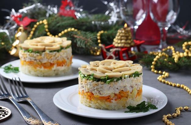Sałatka francuska z kurczakiem, marynowanymi pieczarkami, ziemniakami i marchewką na talerzach. noworoczna kompozycja. format poziomy