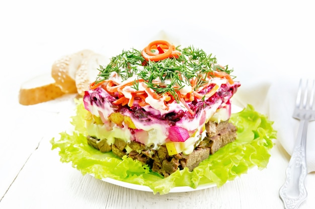 Sałatka francuska z wołowiną, ziemniakami i burakami, gruszkami, koreańską pikantną marchewką, doprawiona majonezem i przyozdobiona koperkiem na zielonej sałacie w talerzu, ręczniku, chlebie na jasnym tle drewnianej deski