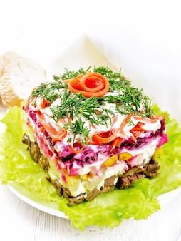 Sałatka francuska z wołowiną, ziemniakami i burakami, gruszkami, koreańską pikantną marchewką, doprawiona majonezem i przyozdobiona koperkiem na zielonej sałacie w talerzu, serwetce, chlebie na drewnianej desce
