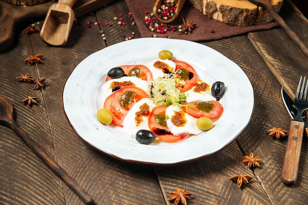 Sałatka gourmet caprese na białym talerzu na drewnianym zdobionym stole