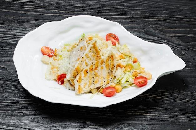 Sałatka grecka cezar z białym mięsem, sałatą i pomidorami koktajlowymi w białej płytce.