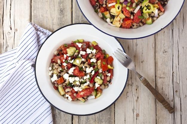 Sałatka grecka na talerzach, a obok widelec i serwetka w paski