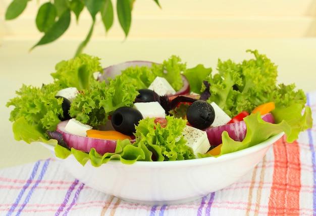 Sałatka grecka na talerzu na stole na jasnym tle