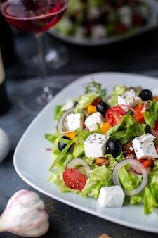 Sałatka grecka pokrojone oliwki czerwone wino wewnątrz białej tablicy