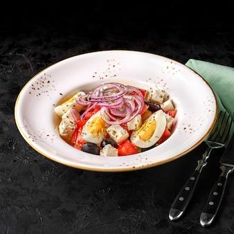 Sałatka grecka, sałatka jarzynowa z jajkiem na twardo, serem feta i oliwkami. selektywne skupienie. menu
