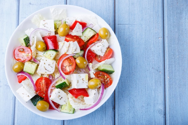 Sałatka grecka tradycyjne greckie danie zdrowe wegetariańskie jedzenie świeże warzywa i ser feta na białym talerzu zbliżenie widok z góry kopia miejsca na tekst