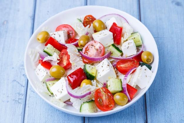 Sałatka grecka tradycyjne greckie danie zdrowe wegetariańskie jedzenie świeże warzywa i ser feta na białym talerzu zbliżenie