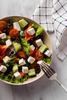 Sałatka grecka w białym talerzu na jasnym tle serwetka i widelec obok siebie