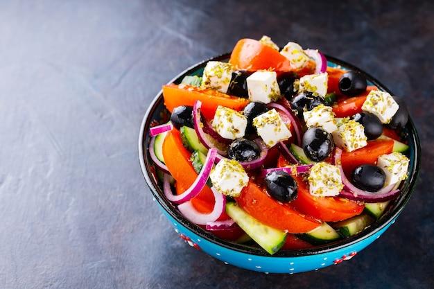 Sałatka grecka w misce na ciemnym tle. zdrowa sałatka z serem feta i oliwkami. sałatka ze świeżych warzyw kuchni śródziemnomorskiej. skopiuj miejsce. widok z góry