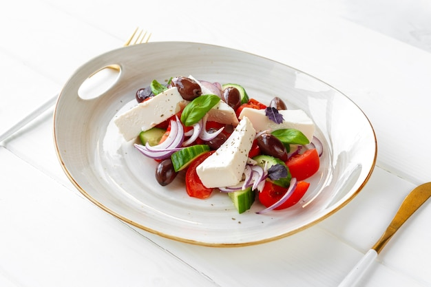 Sałatka grecka w talerzu na białym drewnianym