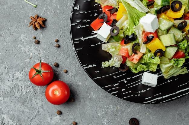 Sałatka grecka z ogórkiem, oliwkami kalamata, serem feta, soczystymi pomidorami wiśniowymi i świeżą bazylią. domowe jedzenie. pomysł na smaczny i zdrowy posiłek wegetariański. widok z góry. skopiuj miejsce.