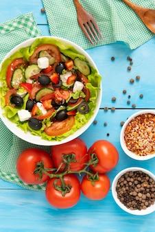 Sałatka grecka z oliwkami, serem feta i świeżymi warzywami na drewnianym niebieskim stole.