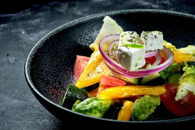 Sałatka grecka z pomidorami, cebulą, papryką i serem feta w czarnej misce na czarnym tle