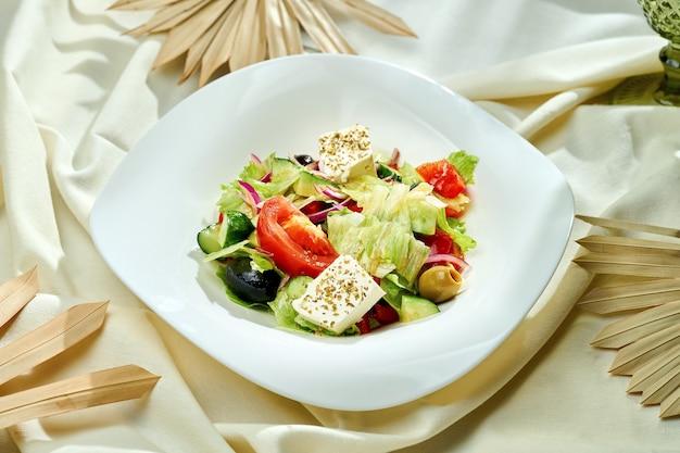Sałatka grecka z pomidorami, oliwkami i serem feta w białym talerzu na obrusie