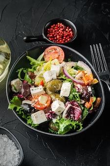 Sałatka grecka z pomidorem, papryką, oliwkami i serem feta, na czarnym tle