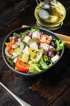Sałatka grecka z pomidorem, papryką, oliwkami i serem feta, na starym ciemnym drewnianym stole w tle