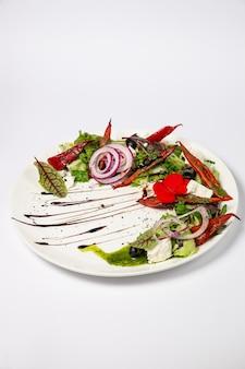 Sałatka grecka ze świeżego ogórka, pomidora, papryki słodkiej, sałaty, czerwonej cebuli, sera feta i oliwek z oliwą. na białej powierzchni
