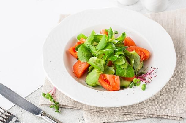 Sałatka grecka ze świeżego ogórka, pomidora, słodkiej papryki, sałaty, czerwonej cebuli, sera feta i oliwek z oliwą z oliwek na białym tle na białym marmurze. domowe jedzenie. smaczne śniadanie. selektywne ustawianie ostrości