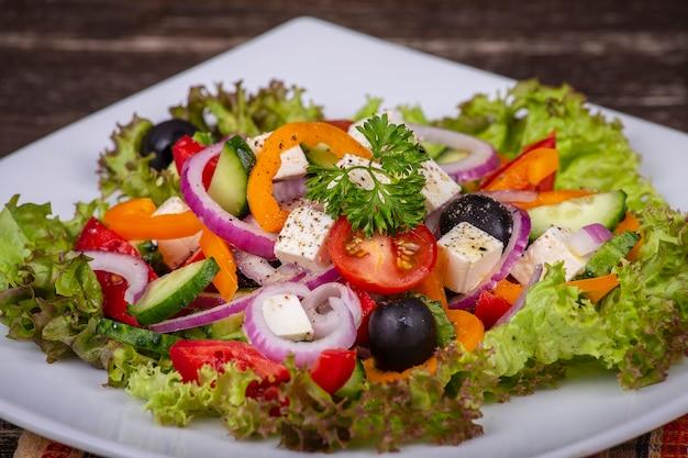 Sałatka grecka ze świeżych warzyw w białym talerzu na drewnianym stole, z bliska