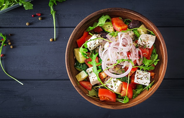 Sałatka grecka ze świeżym pomidorem, ogórkiem, czerwoną cebulą, bazylią, serem feta, czarnymi oliwkami i włoskimi ziołami. widok z góry