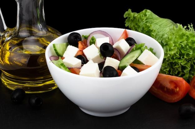 Sałatka grecka ze świeżymi warzywami, serem feta i czarnymi oliwkami na ciemnym tle.