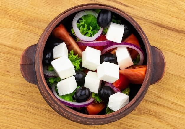 Sałatka grecka ze świeżymi warzywami, serem feta i czarnymi oliwkami na drewnianym tle.