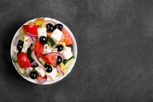 Sałatka grecka ze świeżymi warzywami, serem feta i czarnymi oliwkami. widok z góry
