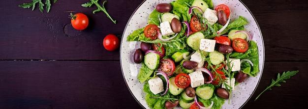 Sałatka grecka ze świeżymi warzywami, serem feta i oliwkami kalamata. zdrowe jedzenie. transparent. widok z góry