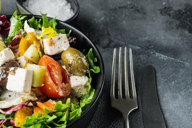 Sałatka grecka ze świeżymi warzywami, serem feta i oliwkami kalamati, na szarym tle