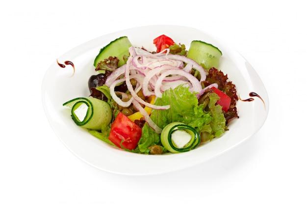 Sałatka grecka ze świeżymi warzywami, serem i oliwkami na białym tle
