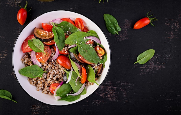 Sałatka gryczana z pomidorami koktajlowymi, czerwoną cebulą i świeżym szpinakiem. wegańskie jedzenie. menu dietetyczne. widok z góry. leżał płasko
