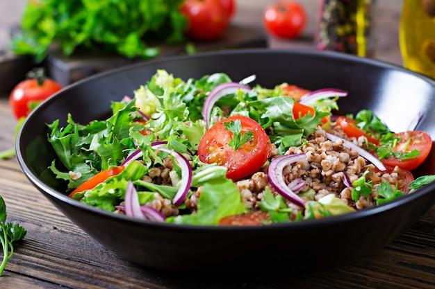 Sałatka gryczana z pomidorami koktajlowymi, czerwoną cebulą i świeżymi ziołami. wegańskie jedzenie. menu dietetyczne.