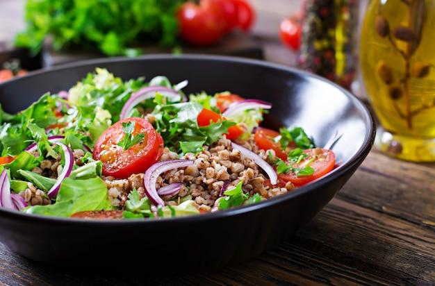 Sałatka gryczana z pomidorkami koktajlowymi, czerwoną cebulą i świeżymi ziołami. wegańskie jedzenie. menu diety.
