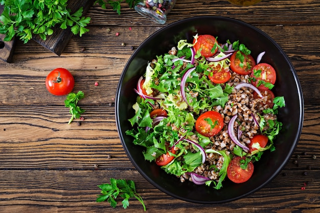 Sałatka gryczana z pomidorkami koktajlowymi, czerwoną cebulą i świeżymi ziołami. wegańskie jedzenie.