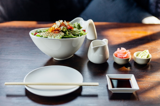 Sałatka japońska z awokado, pomidorem, zielonym dębem, migdałowym i sezamowym dressingiem. podawany z marynowanym imbirem i wasabi.