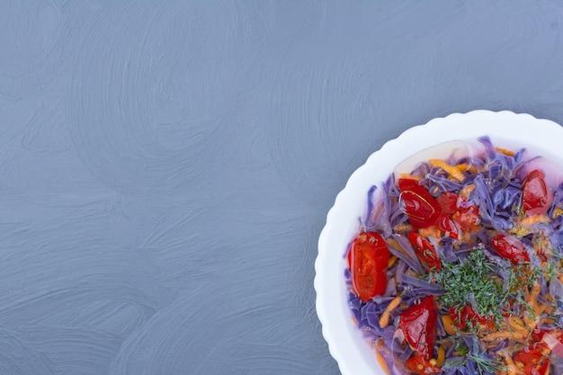 Sałatka jarzynowa i sos z kapustą fioletową w białej ceramicznej misce.