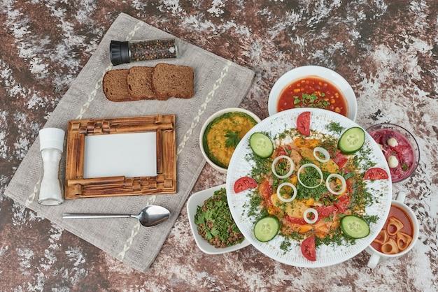 Sałatka jarzynowa na białym talerzu ceramicznym z kolorowymi potrawami.