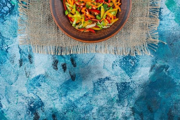 Sałatka jarzynowa na talerzu na konopie, na niebieskim tle.
