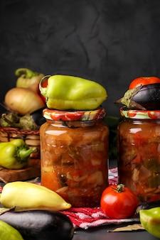 Sałatka jarzynowa z bakłażanem, papryką, cebulą i pomidorami w szklanych słoikach na ciemnej ścianie