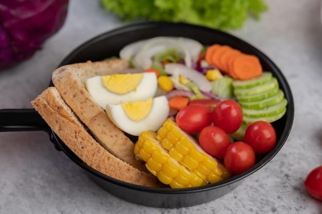 Sałatka jarzynowa z chlebem i gotowanymi jajkami na patelni.